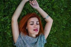 Портрет лета близкий поднимающий вверх милой усмехаясь молодой женщины, кладя на траву, наслаждается ее каникулами Стоковое Изображение RF