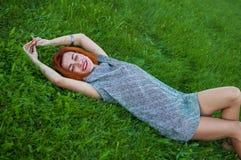 Портрет лета близкий поднимающий вверх милой усмехаясь молодой женщины, кладя на траву, наслаждается ее каникулами, естественными Стоковое Изображение RF