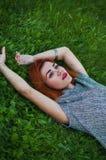 Портрет лета близкий поднимающий вверх милой усмехаясь молодой женщины, кладя на траву, наслаждается ее каникулами, естественными Стоковые Фотографии RF