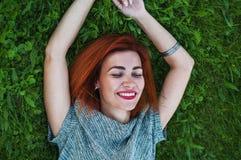 Портрет лета близкий поднимающий вверх милой усмехаясь молодой женщины, кладя на траву, наслаждается ее каникулами, естественными Стоковое Фото