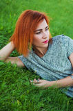 Портрет лета близкий поднимающий вверх милой усмехаясь молодой женщины, кладя на траву, наслаждается ее каникулами, естественными Стоковые Изображения
