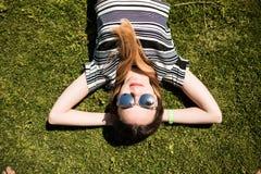 Портрет лета близкий поднимающий вверх милой усмехаясь молодой женщины, кладя на траву, наслаждается ее каникулами Стоковые Изображения RF