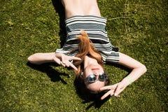 Портрет лета близкий поднимающий вверх милой усмехаясь молодой женщины, кладя на траву, наслаждается ее каникулами Стоковая Фотография
