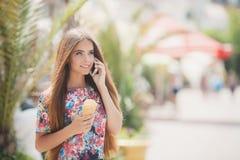 Портрет лета девушки с мороженым, говоря на телефоне Стоковые Фото