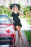 Портрет лета стильной белокурой винтажной женщины при длинные ноги представляя около красного ретро автомобиля модная привлекател Стоковое Изображение
