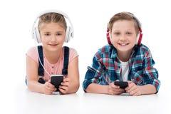 Портрет детей в наушниках с smartphones в руках смотря камеру Стоковая Фотография RF