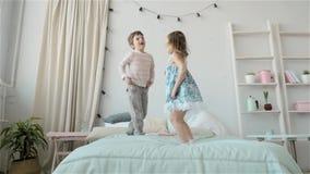 Портрет детей скача на кровать, мальчик и брат и сестра девушки имеют потеху и смеяться над видеоматериал
