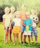 Портрет детей стоя с игрушками на зеленом луге в парке Стоковое Изображение RF