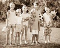 Портрет детей стоя с игрушками на зеленом луге в парке Стоковые Фотографии RF