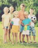 Портрет детей стоя с игрушками на зеленом луге в парке Стоковое Фото