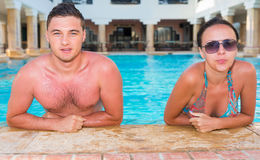 Портрет детеныша suntanned пары ослабляя в бассейне Стоковое фото RF