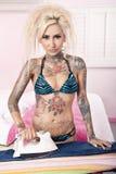 Портрет детенышей татуировал женщину утюжа в спальне стоковые изображения rf