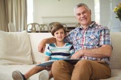 Портрет деда при ее внук держа книгу на софе Стоковые Изображения