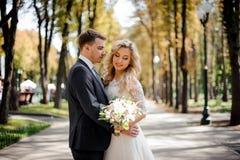 Портрет жениха обнимая белокурую невесту в парке Стоковая Фотография