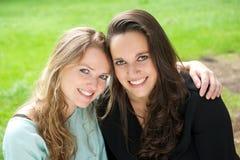 Портрет 2 женских друзей усмехаясь совместно outdoors Стоковые Изображения