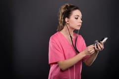 Портрет женских удерживания доктора и smartphone стетоскопа Стоковые Фото