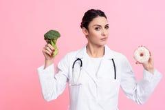 Портрет женского доктора при стетоскоп держа брокколи и донут изолированными Стоковая Фотография