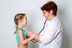 Портрет женского доктора слушая к childs дышая используя стетоскоп стоковые фото