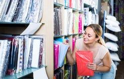 Портрет женского клиента выбирая комплект постельных принадлежностей в магазине Стоковое Фото