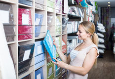 Портрет женского клиента выбирая комплект постельных принадлежностей в магазине Стоковые Фото
