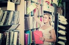 Портрет женского клиента выбирая комплект постельных принадлежностей в магазине Стоковое фото RF