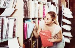 Портрет женского клиента выбирая комплект постельных принадлежностей в магазине Стоковая Фотография