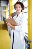 Портрет женского доктора держа ее терпеливую диаграмму в яркой современной больнице Стоковое фото RF