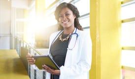 Портрет женского доктора держа ее терпеливую диаграмму на цифровой таблетке в яркой современной больнице Стоковые Изображения