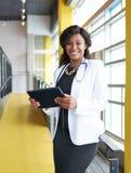 Портрет женского доктора держа ее терпеливую диаграмму на цифровой таблетке в яркой современной больнице Стоковая Фотография