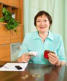 Портрет женского пенсионера с наличными деньгами и счетами Стоковая Фотография