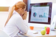 Портрет женского предпринимателя сидя в офисе пока doin Стоковые Фотографии RF
