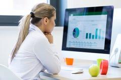 Портрет женского предпринимателя сидя в офисе пока doin Стоковые Изображения RF