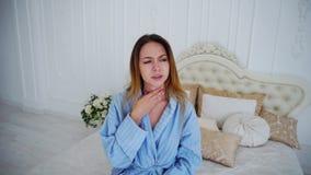 Портрет женского страдания от холодного кашля и боли в горле, смотря камеру стоковые фото