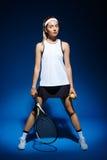 Портрет женского теннисиста с ракеткой и шарика в руке представляя в студии Стоковое Изображение RF