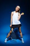 Портрет женского теннисиста с ракеткой и шарика в руке представляя в студии Стоковое Фото