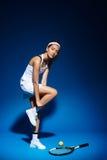 Портрет женского теннисиста с ракеткой и шарика в сторону в студии Стоковое Изображение