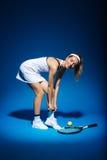 Портрет женского теннисиста с ракеткой и шарика в сторону в студии Стоковая Фотография RF