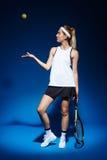 Портрет женского теннисиста с ракеткой и шарика представляя в студии Стоковая Фотография