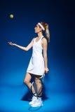 Портрет женского теннисиста с ракеткой и шарика представляя в студии Стоковое Изображение RF
