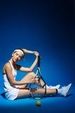 Портрет женского теннисиста с ракеткой и шарика сидя на поле в студии Стоковые Изображения RF