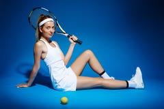 Портрет женского теннисиста с ракеткой и шарика сидя на поле в студии Стоковая Фотография