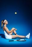 Портрет женского теннисиста с ракеткой и шарика сидя на поле в студии Стоковая Фотография RF