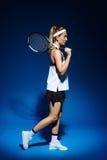 Портрет женского теннисиста с ракеткой на плече представляя в студии Стоковое фото RF