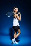 Портрет женского теннисиста с ракеткой на плече представляя в студии Стоковая Фотография RF