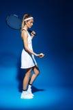 Портрет женского теннисиста с ракеткой на шарике shoulderand в руке представляя в студии Стоковые Фото