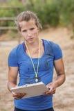 Портрет женского тренера держа доску сзажимом для бумаги во время полосы препятствий Стоковые Изображения