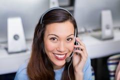 Портрет женской исполнительной власти обслуживания клиента говоря на шлемофоне на столе Стоковые Фотографии RF
