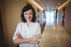 Портрет женской исполнительной власти стоя с оружиями пересек в коридор Стоковые Изображения