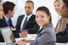 Портрет женской исполнительной власти с встречей офиса в предпосылке Стоковая Фотография RF