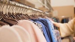 Портрет женщина в стеклах на магазине одежды выбрал де-сфокусированное платье - Стоковое Изображение
